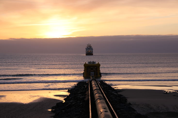 Offshore and energy industry on the beach with sunrise behind the sea