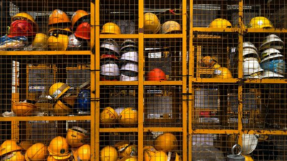 yellow, white and orange safety head work-wear placed on handrails and mesh wire panels